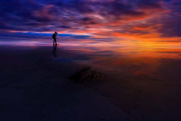 Reflexion des fotografen mit erstaunlichem himmel des zeitsonnenuntergangs