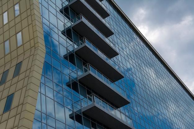Reflexion des himmels und der wolken in den fenstern eines mehrstöckigen glasgebäudes.