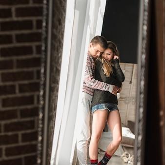 Reflexion des jungen mannes ihre freundin von hinten im spiegel umfassend