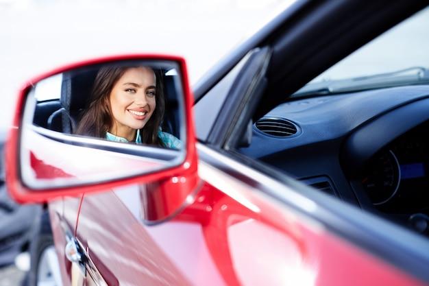 Reflexion des mädchens, das im roten auto sitzt, glücklicher fahrer. frau, die rückspiegel betrachtet. porträt der glücklichen frau im auto
