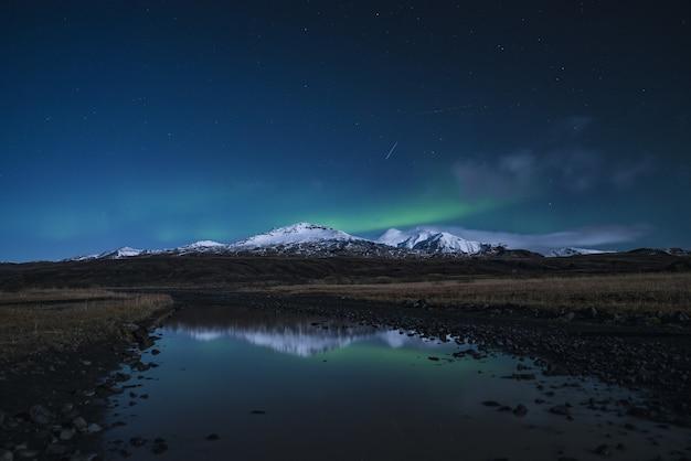 Reflexion des schneebedeckten berges auf fluss während der nacht