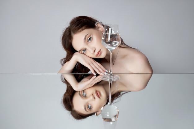 Reflexion einer frau im spiegel mit glas in der hand. schönes gesichts make-up, naturkosmetik