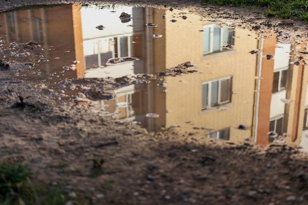 Reflexion eines mehrfamilienhauses in wasserpfützen im herbst nach regen.
