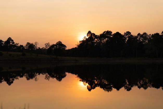 Reflexion eines sonnenuntergangs durch einen see innerhalb des nationalparks khao yai, thailand