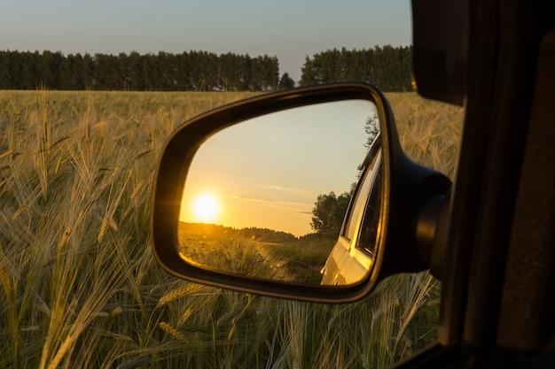 Reflexion im sonnenuntergangspiegel auf dem weizengebiet