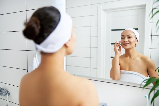 Reflexion im spiegel einer lächelnden frau, die make-up entfernt und ihr gesicht mit mizellenwasser reinigt