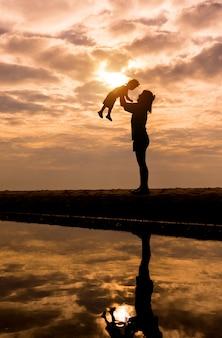 Reflexion silhouettemother mit ihrem kleinkind gegen den sonnenuntergang