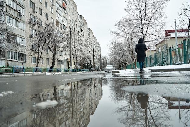 Reflexion über die pfütze der schneebedeckten stadtlandschaft im winter