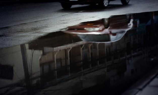 Reflexion verschwommener autos in pfütze auf der stadtstraße nach starkem regenfall, selektiver fokus. regenzeit, transporthintergrund.