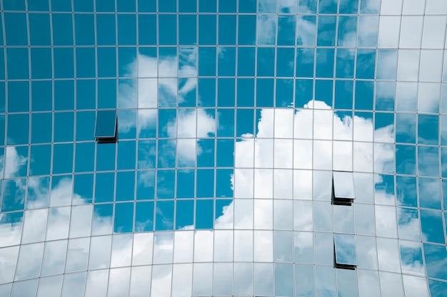 Reflexion von blauem himmel und wolken in einem modernen hochhaus.