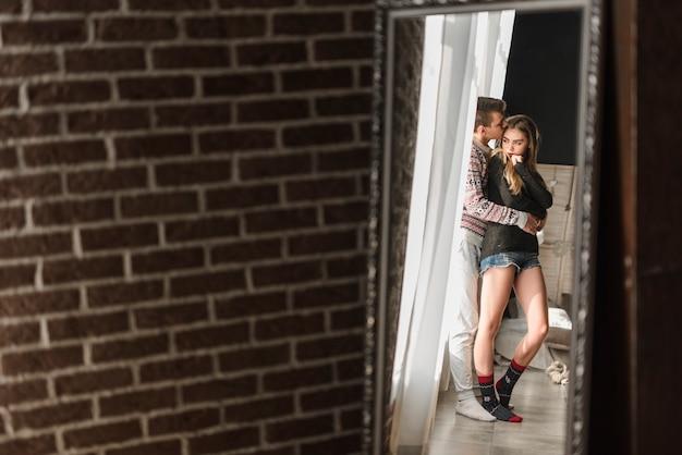 Reflexion von liebevollen jungen paaren im spiegel nahe der backsteinmauer