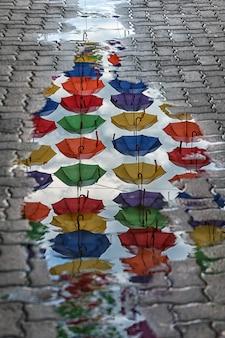 Reflexion von regenschirmen in einer pfütze auf der straße.