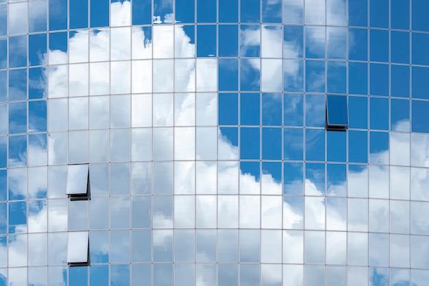 Reflexion von wolken in einem modernen gespiegelten bürogebäude.