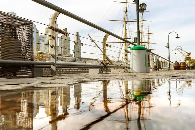 Reflexionen von gebäuden und anderen objekten in der wasseroberfläche der straße nach einem regen.