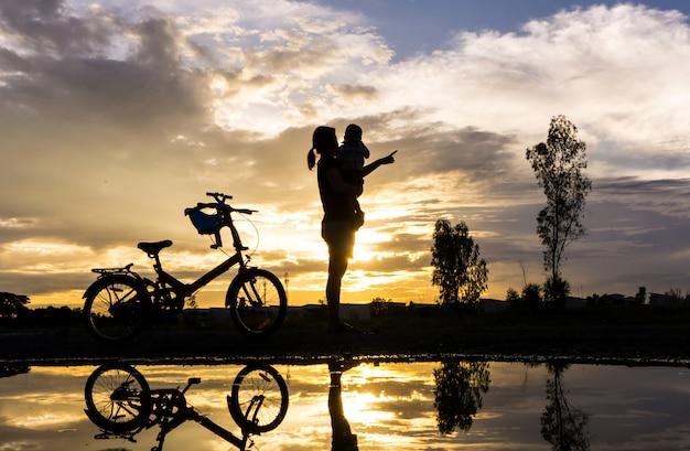 Reflexions-schattenbild der mutter mit ihrem kleinkind gegen den sonnenuntergang.