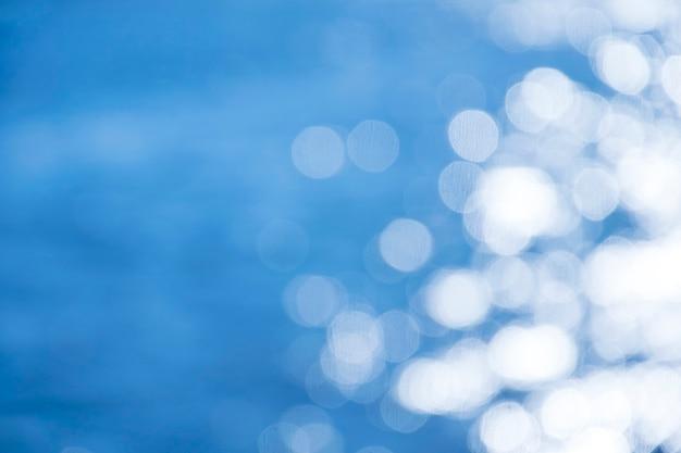 Reflexionslicht auf blauem meer defocused abstrakten lichtern.
