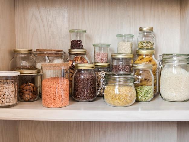 Regal in der küche mit verschiedenen müsli und samen