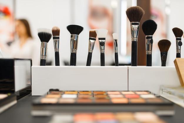 Regal mit schatten und pinseln im kosmetikgeschäft, niemand. luxus-schönheitssalon, schaufenster mit produkten auf dem modemarkt