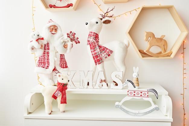 Regal mit weihnachtsfiguren weihnachtsmann und hirsch im kinderzimmer. weihnachtsinnenraum des kinderzimmers