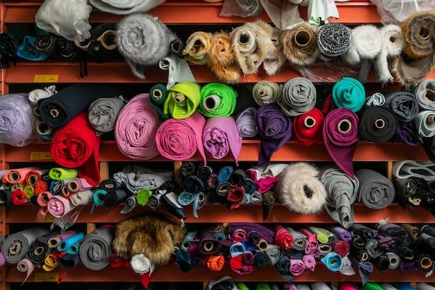 Regale mit ausgelegten rollen aus mehrfarbigem stoff