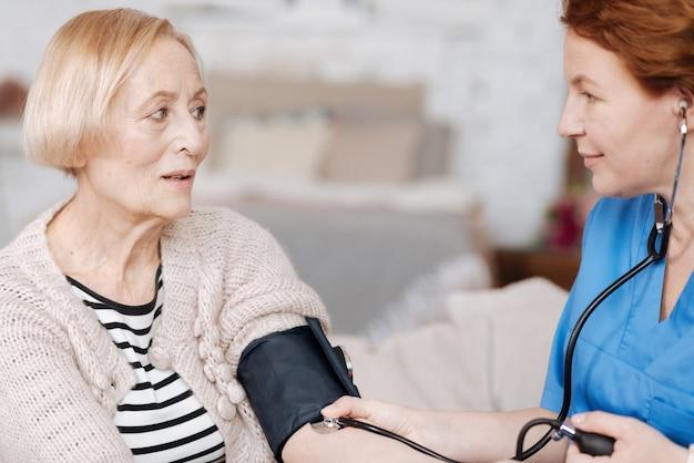 Regelmäßige tests zu hause. ordentliche, anmutige medizinische mitarbeiterin, die ihrer patientin einen besuch abstattet, um eine untersuchung durchzuführen und sich um eine ältere dame zu kümmern