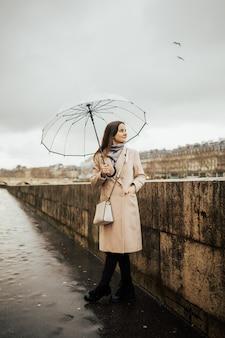 Regen an einem wintertag in der stadt, frau mit transparentem regenschirm, der auf einer straße nahe fluss seine steht.