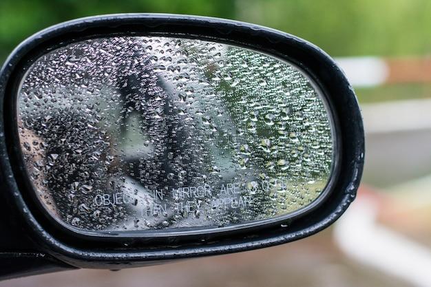 Regen auf einem autospiegel. herbststimmung. herbstwetter mit dem auto reisen.