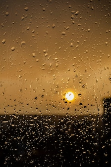 Regen außerhalb fenster auf hintergrund des sonnenuntergangs. bei regen fällt regen auf glas. sonnenuntergang außerhalb des fensters während des regens. helle textur von wassertropfen