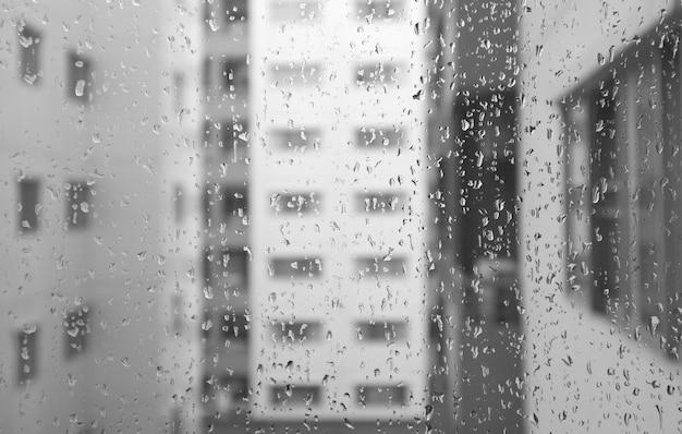 Regen fällt auf fensterglas mit verschwommenen modernen gebäuden