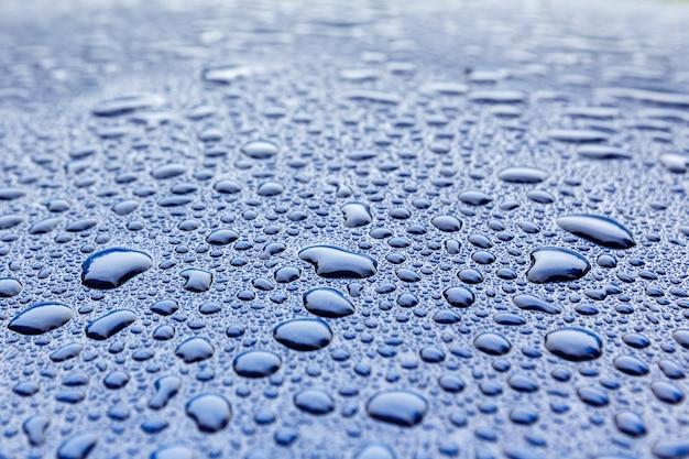Regen lässt nahaufnahme auf einer blauen autokarosserie mit hydrophobem effekt fallen.