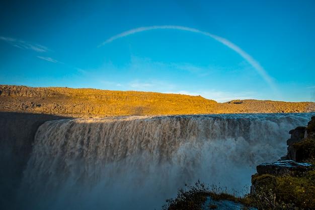 Regenbogen am dettifoss wasserfall, island. der größte wasserfall der europäischen gemeinschaft