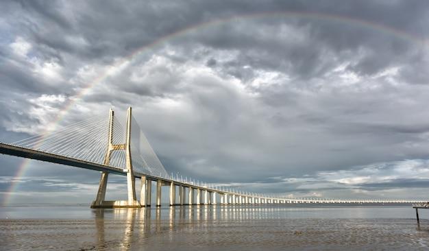Regenbogen auf der vasco de gama-brücke, lissabon, portugal