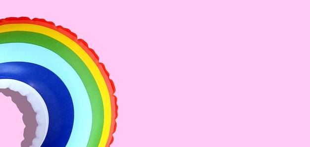 Regenbogen aufblasbarer schwimmbadring auf rosa hintergrund.