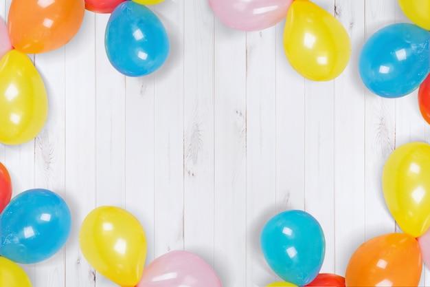 Regenbogen ballons auf dem bretterboden. hohe draufsicht.