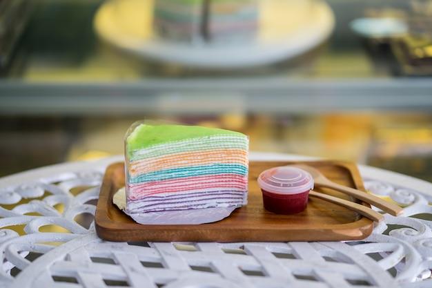 Regenbogen-crêpe-kuchen mit erdbeermarmelade auf holzteller