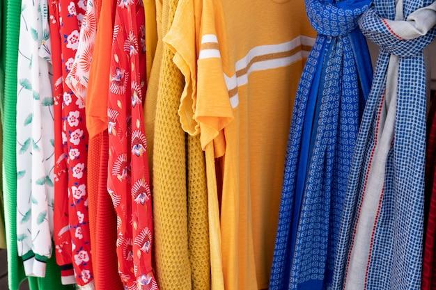 Regenbogen farbige kleidung auf kleiderbügeln in einem einzelhandelsgeschäft