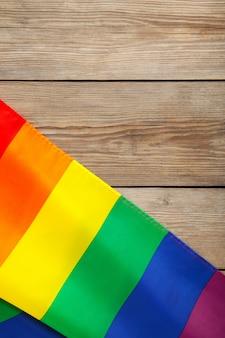 Regenbogen-lgbt-flagge auf grauem hölzernem hintergrund mit kopienraum. vertikales foto
