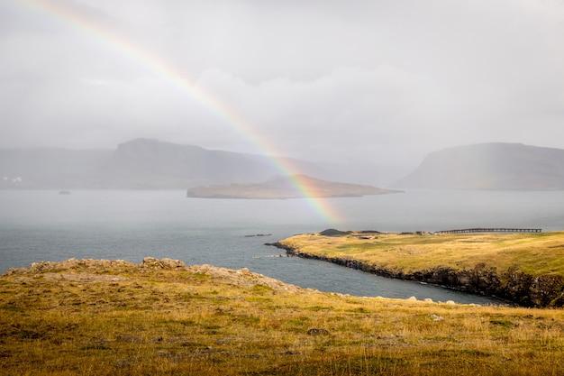 Regenbogen über dem see mit den silhouetten der klippen in island