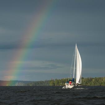 Regenbogen über einem see mit einem segelboot, see des holzes, ontario, kanada