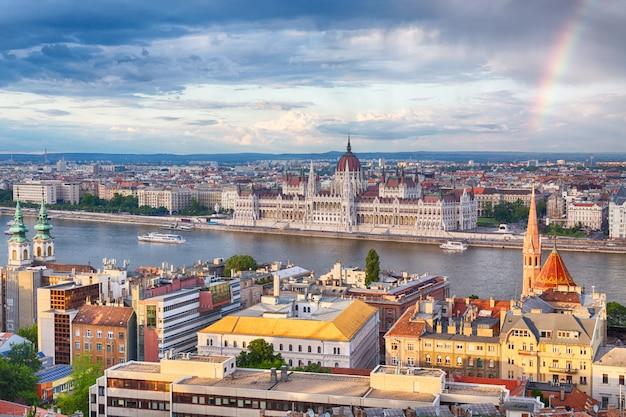 Regenbogen über parlament und flussufer in budapest ungarn
