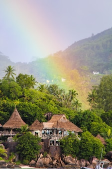Regenbogen über tropischer insel und luxuriösem hotel in seyshelles