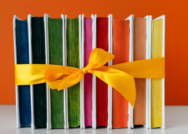 Regenbogenbücher stapeln mit gelbem band