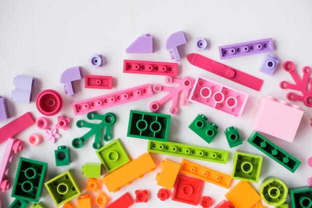 Regenbogenfarben. bunter plastikerbauer, spielzeugdetails über einen blauen hintergrund. teile von hellen kleinteilen für den bau.