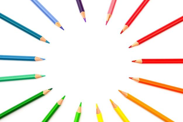 Regenbogenfarbene bleistifte liegen auf einem weißen hintergrund und bilden einen leeren kreis in der mitte