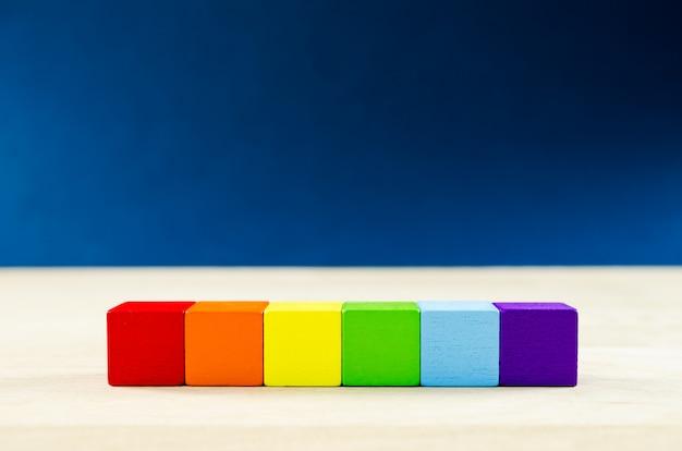 Regenbogenfarbene holzklötze in einem konzeptuellen bild für lesben-, schwulen-, bisexuellen-, transgender-, queer-gemeinschaft.