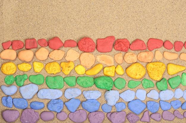 Regenbogenfarbene steine liegen auf dem sand