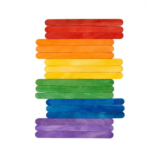 Regenbogenfarbenes hölzernes eis klebt auf weißem mehrfarbigem abstraktem lgbt-konzept