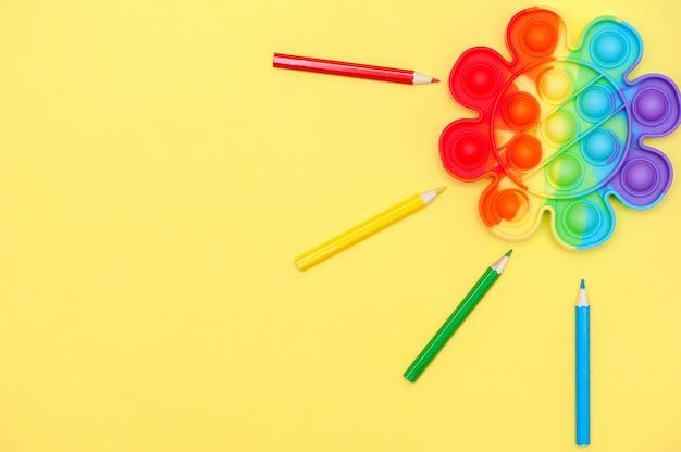 Regenbogenfarbenes spielzeug anti-stress für die finger pop it in form einer blume auf gelbem hintergrund kindheitskonzept