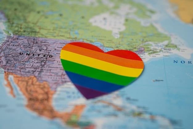 Regenbogenfarbherz auf amerika-globus-weltkarte