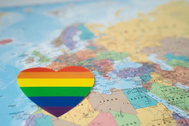 Regenbogenfarbherz auf europa-weltkarte, symbol des lgbt-stolzmonats.
